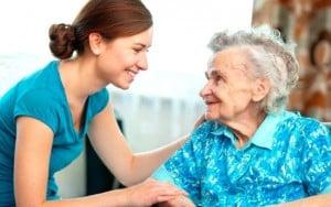 aidante qui sourit a une personne âgée