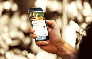 Main tenant un smartphone ou l'on voit Smartbnb