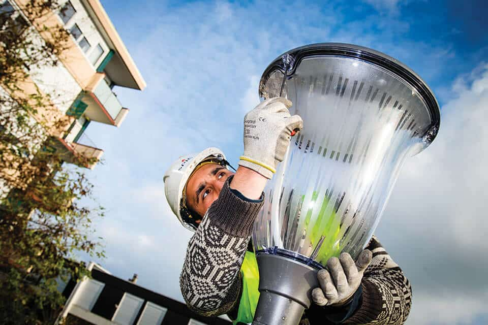 un employé travaillant sur un lampadaire de l'éclairage public