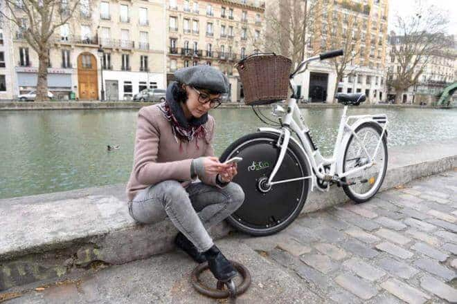 une jeune fille assise au bord du canal Saint Martin à coté de son vélo électrique solaire
