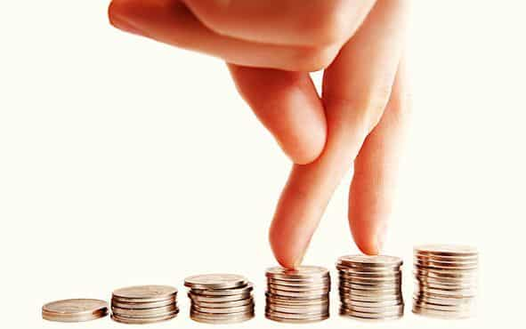 Doigts posés sur des petites piles de pièces de monnaie