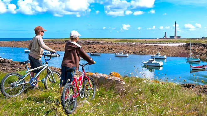 Deux enfants avec leurs velos devant la mer