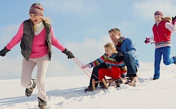 Famille qui s'amuse aux sports d'hiver
