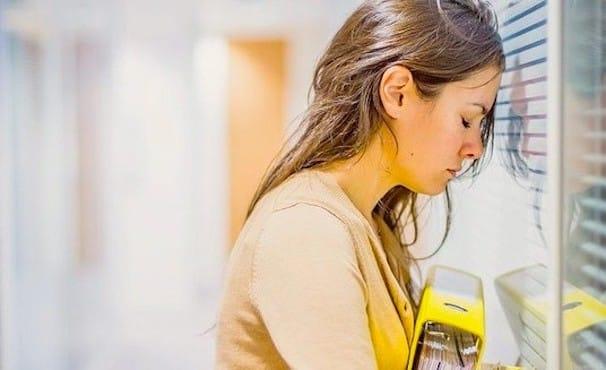 Femme appuyee contre un store