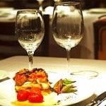 Deux verres posés sur une table, devant une assiette.