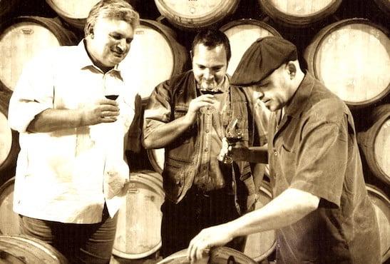 Trois hommes qui degustent du vin.