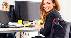 Jeune femme au travail, assise dans un fauteuil roulant.