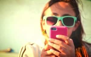 Jeune femme à lunettes regardant son smartphone