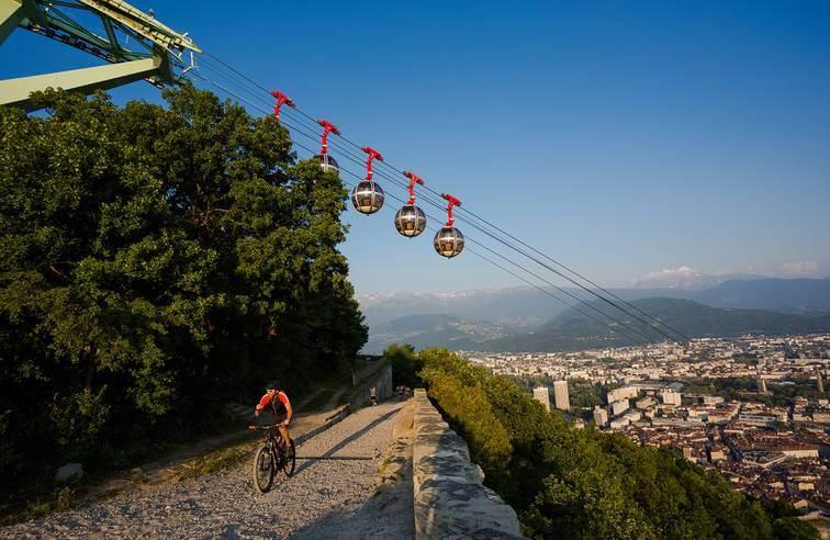 Grenoble: le téléphérique passant au dessus d'une route où passe un vélo