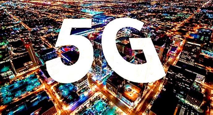 Deux grandes lettres 5G au-dessus d'une ville, la nuit.