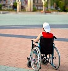 Adolescent de dos dans une fauteuil roulant