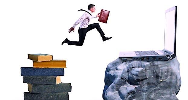 Homme qui saute entre des livres et un ordinateur