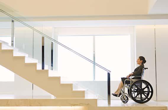 Personne en fauteuil roulant face a un escalier