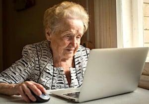 Une femme âgée devant son écran en usage d'Internet
