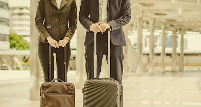Un couple tenant des valises a roulettes
