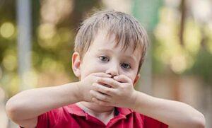 Enfants qui met ses mains devant sa bouche.