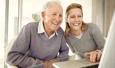 Un senior et une jeune femme devant un ordinateur.