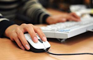 Mains qui utilisent un clavier et une souris d'ordinateur.