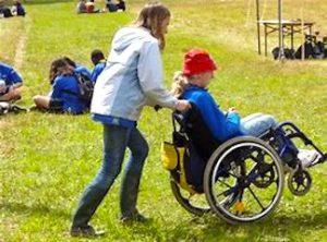 le collectif Merci Raymond engagé dans les aidants comme sur cette photo avec cette personne qui pousse une personne en fauteuil