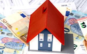 Une petite maison posée sur des billets de banque.