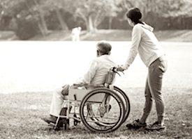 Une aidante avec une personne en fauteuil roulant.