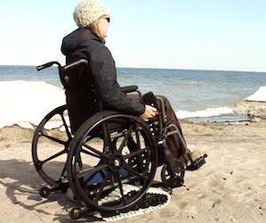 Personne dans un fauteuil roulant sur une plage.