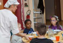 une cantine scolaire avec des enfants servis par une employée