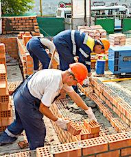 vue de maçons avec des briques pour palier le manque de logements en construction